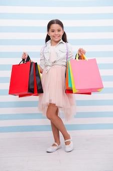 쇼핑은 그녀가 가장 좋아하는 활동입니다. 어린 소녀 쇼핑백 줄무늬 배경을 운반합니다. 모든 연령대의 여성들은 쇼핑을 좋아합니다. 꼬마 소녀는 쇼핑 세일 시즌을 즐깁니다. 만족한 얼굴로 웃고 있는 소녀는 가방을 들고 있습니다.