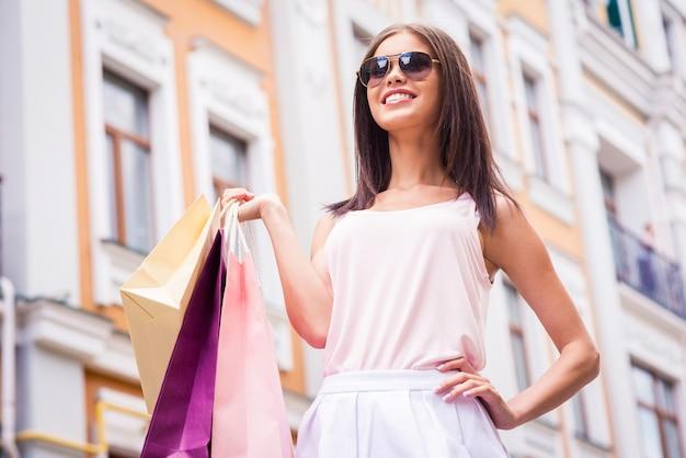 쇼핑은 내 인생! 선글라스를 끼고 쇼핑백을 들고 야외에 서 있는 동안 멀리 바라보는 아름다운 젊은 여성의 낮은 각도