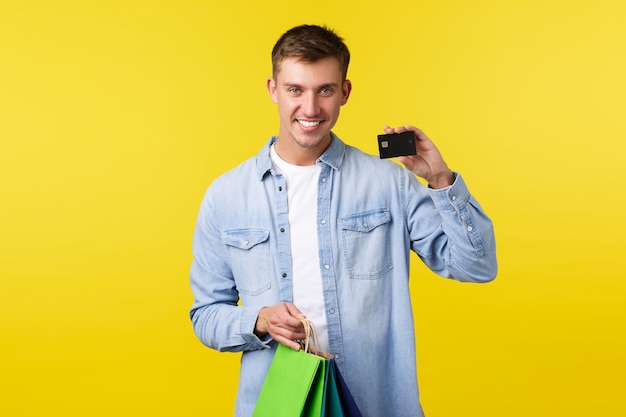 Shopping, leisure and discounts concept. smiling handsome young man buying new clothes, holding bags and showing credit card with satisfied expression, paying with saved money, yellow background.