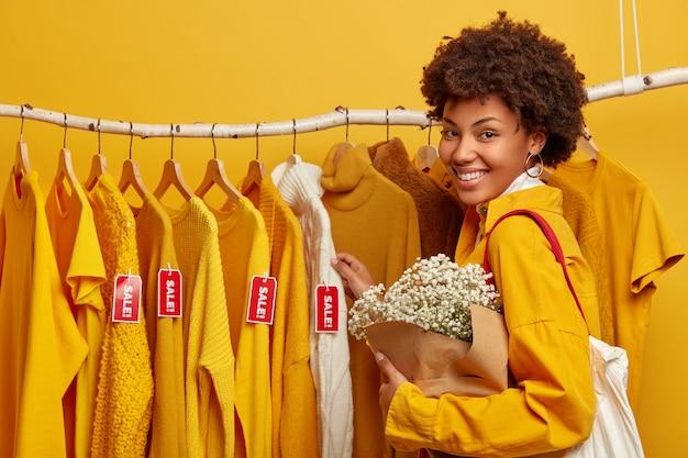 쇼핑 라이프 스타일 개념. 긍정적 인 여성 쇼핑객은 주말을 세련된 상점에서 보내고 꽃다발을 들고 의류 선반 근처에 서 있습니다. 큰 세일