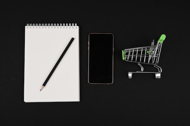 쇼핑리스트. 노트북 및 검정색 배경에 연필입니다. 복사 공간 쇼핑 바구니