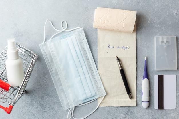 Список покупок на туалетной бумаге медицинская маска корона вирус концепция кредитная карта маленькая корзина