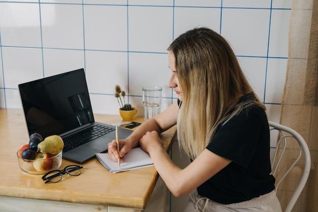 쇼핑 목록 온라인 쇼핑은 노트북 근처에 앉아 쇼핑 목록을 작성하는 젊은 여성의 돈을 절약합니다.