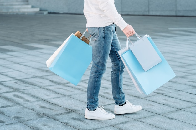 Shopping man casual urban consumerism legs in jeans paper bags in hands