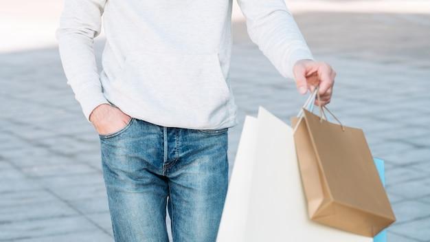 ショッピングマンカジュアルな都会の消費主義手に紙袋