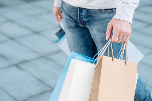 Shopping man casual urban consumerism paper bags variety in hands