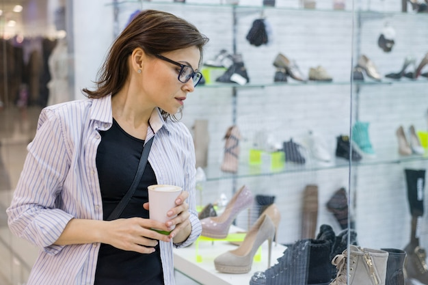 Shopping mature woman, female looking at a shop window with shoes