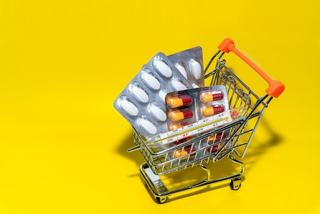 ショッピング医学の概念。さまざまなカプセル、錠剤、薬、ショップのトロリーに温度計。ヘルスケアと製薬会社のための独創的なアイデア。