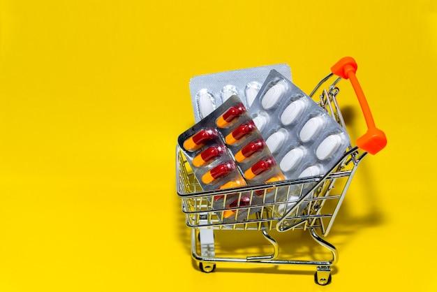 ショッピング医学の概念。黄色の背景にショップトロリーで様々なカプセル、錠剤、薬。