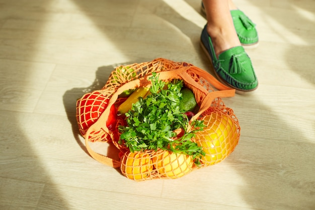 Shopping mesh bag full of fresh fruits and vegetables on the floor at home