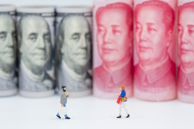 Shopping miniature figures with us dollar and china yuan banknotes.