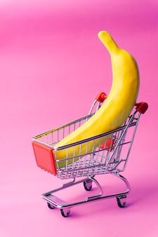 Shopping minimal concept. banana in a toy shopping cart.