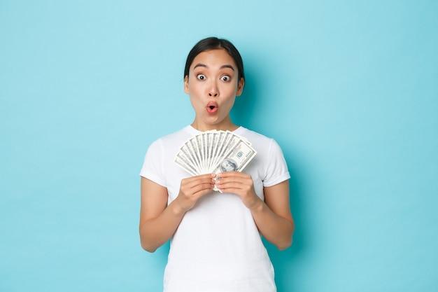 Покупки, деньги и концепция финансов. возбужденная счастливая азиатская девушка показывает наличные деньги в долларах и радуется, зарабатывает первую зарплату, получает зарплату или повышение, приподнятая над голубой стеной