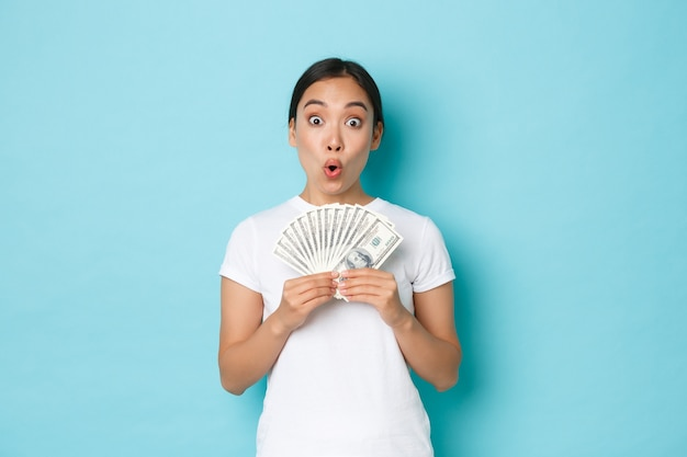Shopping, money and finance concept. excited happy asian girl showing cash of dollars and rejoicing, earn fist paycheck, receive salary or raise, standing upbeat over light-blue wall