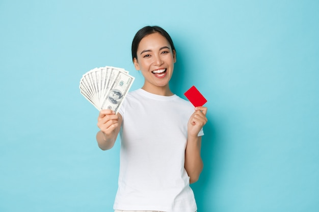Shopping, money and finance concept. happy carefree asian girl in white t-shirt holding credit card but choosing cash instead. dont like contactless payment, smiling upbeat, blue wall