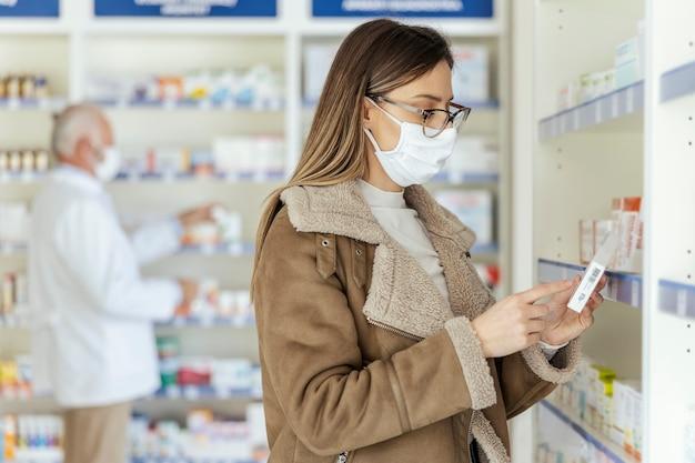 약국 및 약국에서 의약품 쇼핑. 안경을 쓰고 얼굴에 보호 마스크를 쓴 아름다운 소녀의 클로즈업 샷이 약과 보충제 상자에서 선언문을 읽고 있다