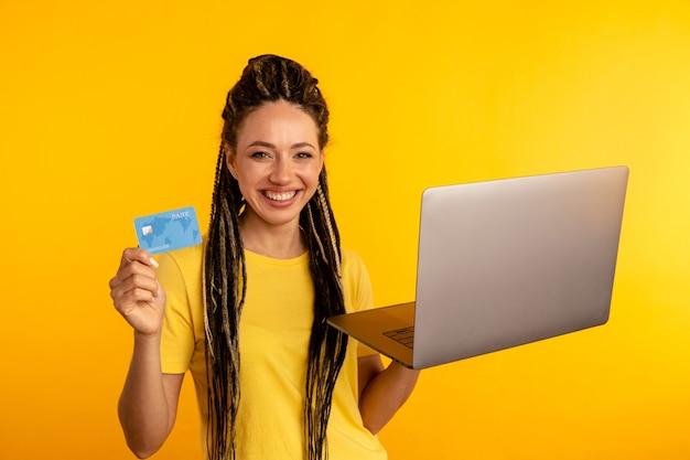 Покупки на компьютере. улыбающаяся женщина с ноутбуком и кредитной картой, делая покупки в интернете.