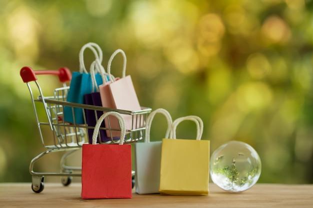 쇼핑 온라인 및 전자 상거래 개념 : 쇼핑 카트 및 크리스탈 글로브에 종이 봉지. 온라인 상점은 기업가와 고객 간의 상품 거래의 또 다른 매체로 간주됩니다.