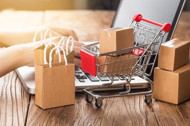 집 개념에서 온라인 쇼핑. 노트북 키보드에 장바구니에 판지.