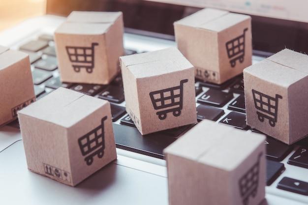 Покупки онлайн. картонная коробка с логотипом корзины на клавиатуре ноутбука. сервис покупок в интернете. предлагает доставку на дом