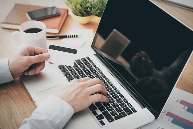 オンラインショッピング。ノートパソコンで作業し、木製の机に座ってクレジットカードを保持している男性のクローズアップ上面図