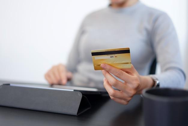 オンラインショッピングのコンセプトは、クレジットカード情報をショッピングアプリケーションに挿入してオンライン商品を購入する中年女性の女性です。