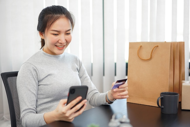オンラインショッピングのコンセプト女性の買い物客は、オンラインショップで商品を選んだり購入したりすることを楽しんでいます。