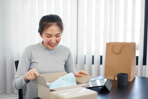 Концепция покупок в интернете: улыбающаяся женщина распаковывает прибывающую посылку, чтобы проверить продукты, которые она купила после долгого ожидания.