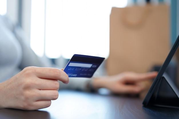 オンラインショッピングの概念オンラインショッピングアプリケーションでのオンライン購入を容易にするためにクレジットカードを使用する若い女性。