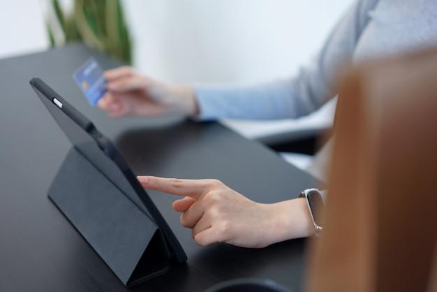 Концепция покупок в интернете молодая женщина, использующая свою кредитную карту для облегчения онлайн-покупок в приложении для онлайн-покупок.
