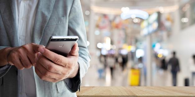 ショッピングのオンラインコンセプト。スマートフォンアプリでオンラインショッピングのビジネスマン
