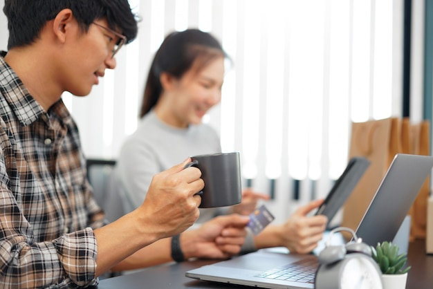 Shopping online concept a couple choosing recommended products with appealing promotions shown in online shop on a tablet device.