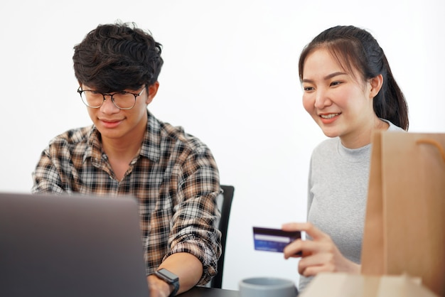 Shopping online concept a couple enjoying online shopping and buying many stuffs by a credit card.