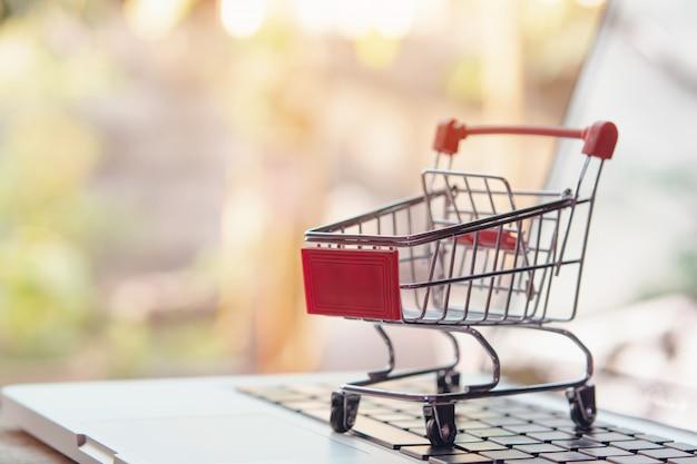 온라인 개념 쇼핑. 빈 쇼핑 카트 또는 노트북 키보드에 트롤리. 온라인 웹에서 쇼핑 서비스. 택배를 제공합니다.