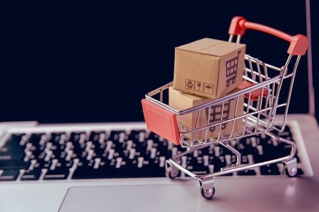 쇼핑 온라인 개념-노트북 키보드에 트롤리에 쇼핑 카트 로고와 함께 소포 또는 종이 상자. 온라인 웹에서 쇼핑 서비스. 택배를 제공합니다.