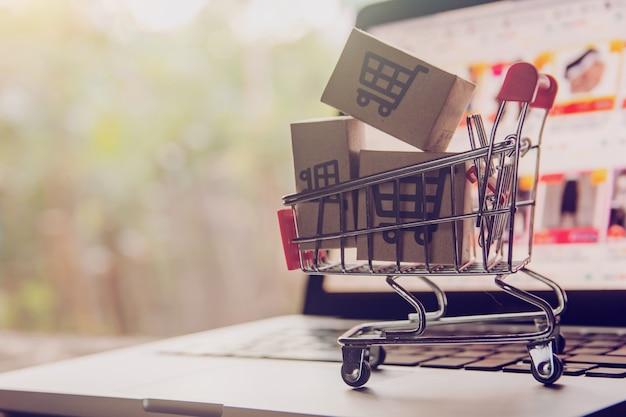 온라인 개념 쇼핑. 노트북 키보드에 트롤리에 쇼핑 카트 로고가있는 소포 또는 종이 상자. 온라인 웹에서 쇼핑 서비스. 택배를 제공합니다.