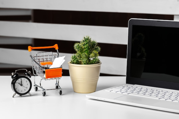 Shopping online concept. small toy trolley and gadgets on the table
