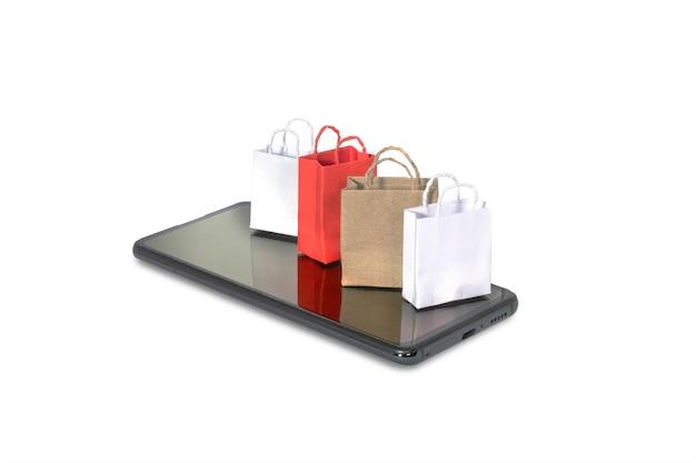 白で隔離されるスマートフォンの紙袋でオンラインショッピングのコンセプト。