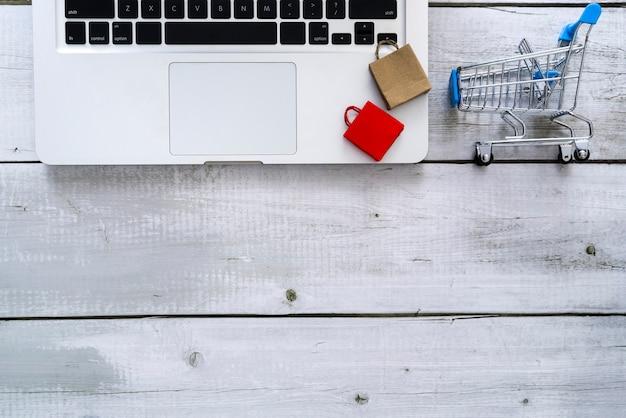 Концепция онлайн-покупок с бумажными пакетами для ноутбуков и тележкой с копией пространства для текста