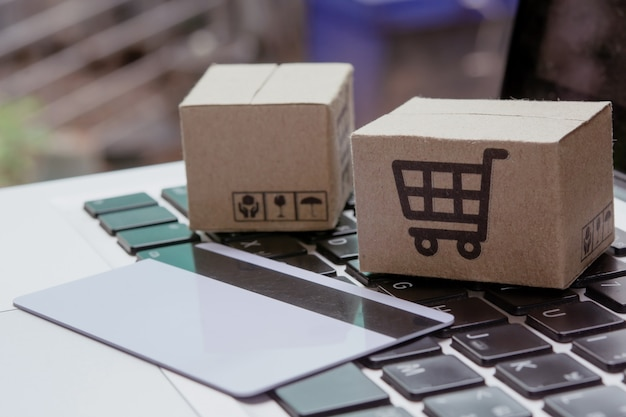 オンラインショッピング。ノートパソコンのキーボードにショッピングカートのロゴが付いたクレジットカードと段ボール箱。オンラインウェブ上のショッピングサービス。宅配を提供しています