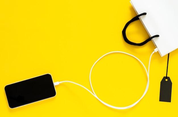スマートフォンからオンラインショッピングを充電器ワイヤーで買い物袋に接続します。サイバーマンデーとブラックフライデーのコンセプト。