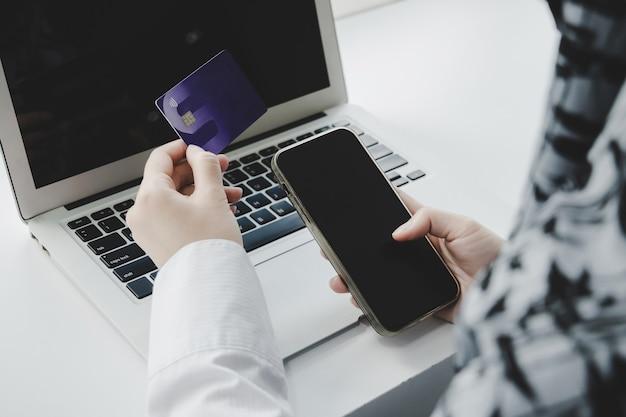온라인 쇼핑. 홈 오피스, 인터넷, 디지털 마케팅, 모바일 뱅킹, 온라인 지불 및 디지털 기술 개념의 책상 위에 있는 노트북 컴퓨터에서 신용 카드와 온라인 쇼핑을 손에 들고