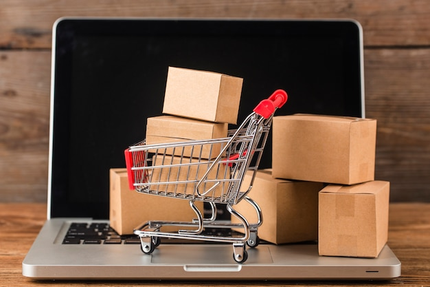 Shopping online at home concept. cartons in a shopping cart on a laptop keyboard.