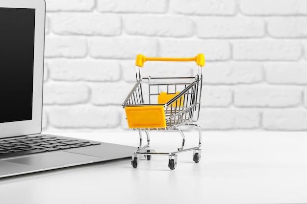 Shopping online  : mini shopping cart and laptop