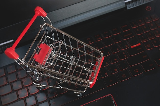 Shopping online   shopping cart on the black keyboard. red mettal trolley on a laptop keyboard. shopping service on the online web. offers home delivery. copyspace for text.