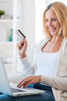 オンラインショッピング。ソファに座ってインターネットで買い物をしている成熟した女性の笑顔
