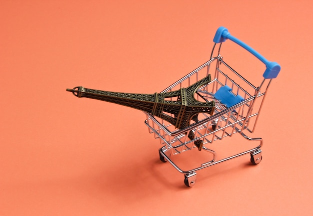 Shopping in paris minimalistic concept. shopping trolley, eiffel tower figurine on coral colored background.