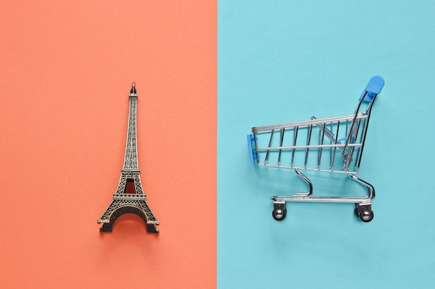 Shopping in paris minimalistic concept. shopping trolley, eiffel tower figurine on pastel colored background. top view