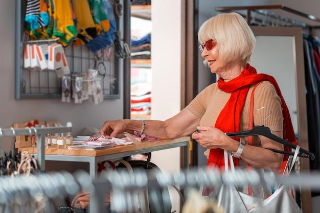 ショッピングプロセス。彼女の顔に興味を示しながら彼女の新しいドレスのために追加の衣服を選択する年配のファッショナブルな白髪の女性のプロフィール