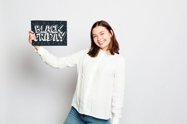 쇼핑, 소매, 검은 금요일, 판매, 쇼핑, 그리고 사람들의 개념 - 웃고 있는 젊은 브루네트 소녀가 검은 금요일 표지판을 들고 있습니다. 블랙프라이데이 세일.